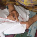 A woman practices her embroidery skills