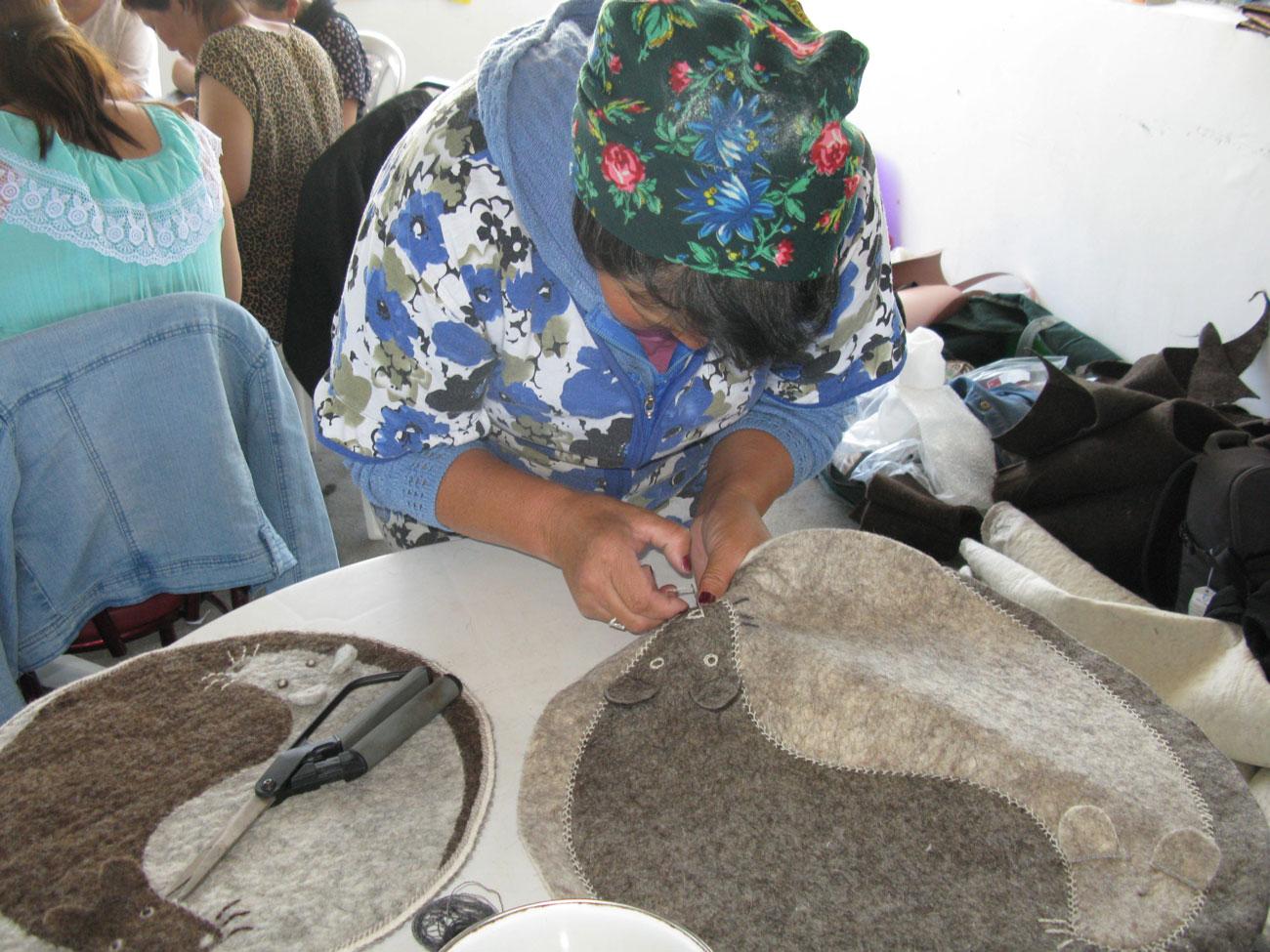 An artisan adds the final stitches to a felt pet mat
